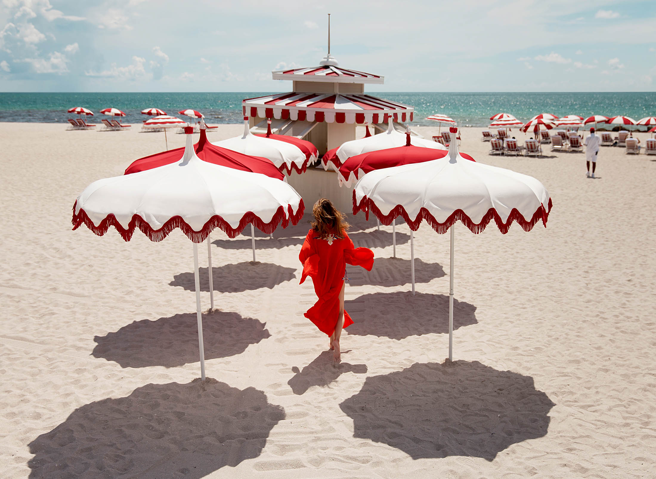 woman walking on the beach surrounded by white and red umbrellas
