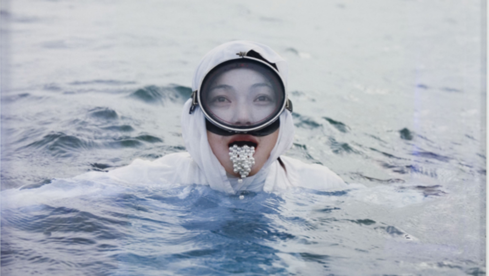 Woman swimming in sea with pearls falling out of mouth