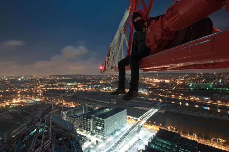 Man sitting on crane above city