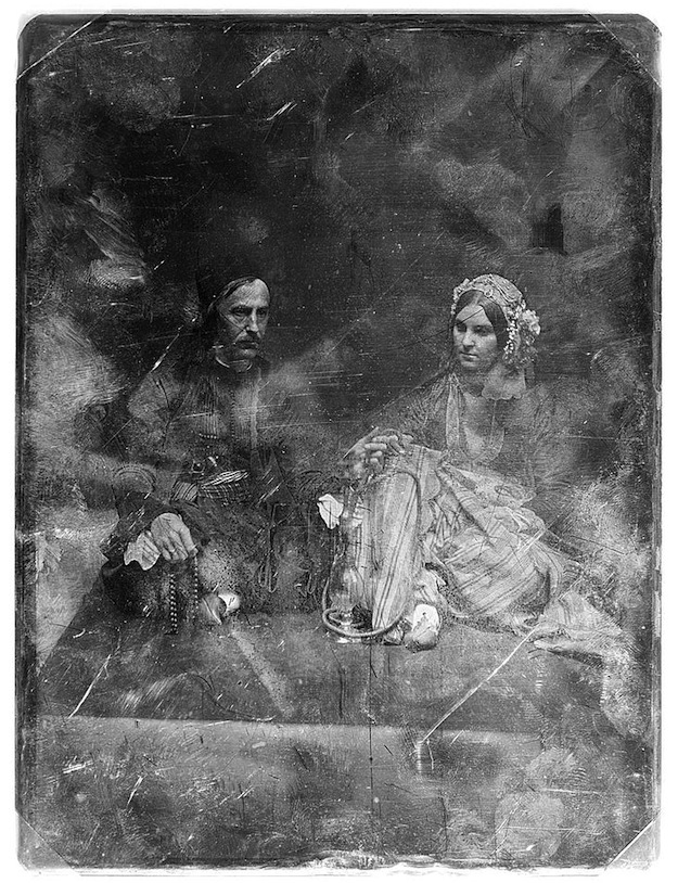 Daguerreotype portrait of a woman and man holding items