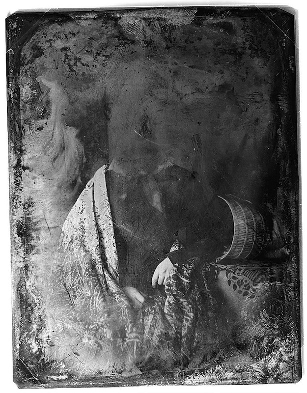 Daguerreotype portrait of a woman resting her head on a table