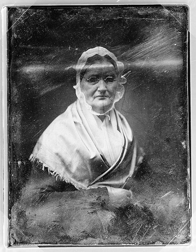 A daguerreotype portrait of an elderly woman in glasses