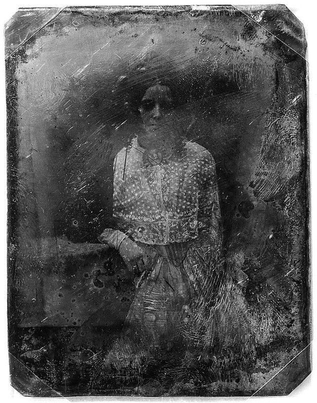 Daguerreotype portrait of a young girl in a dress, standing with her arm resting on a table