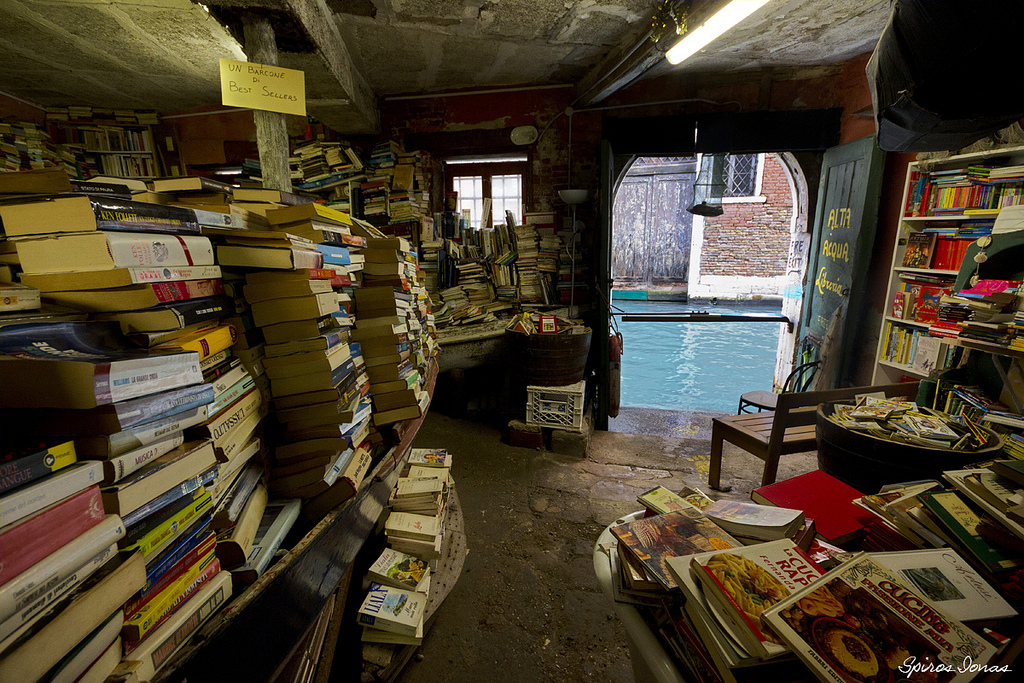 piles of books in a books store looking over the canal