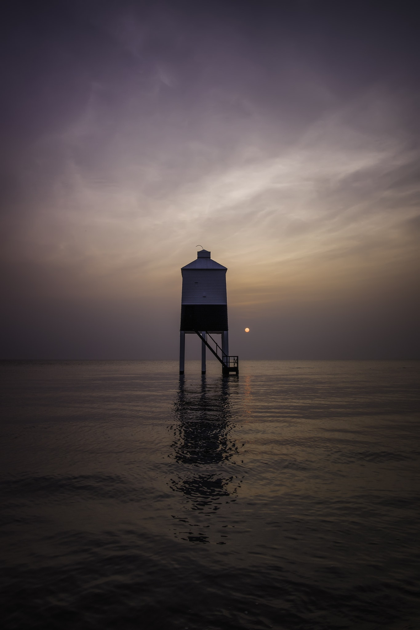 Lighthouse on stilts surrounded by water