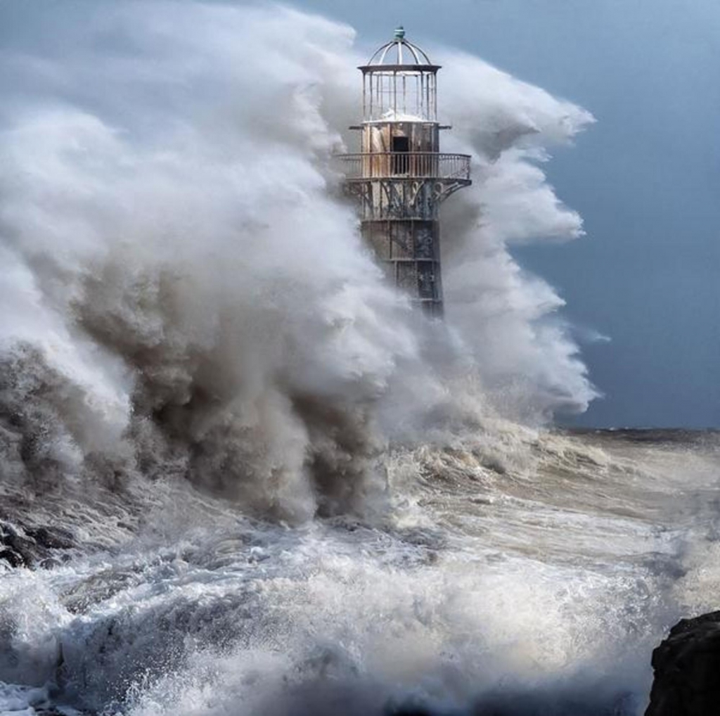 Waves crashing over Whiteford lighthouse
