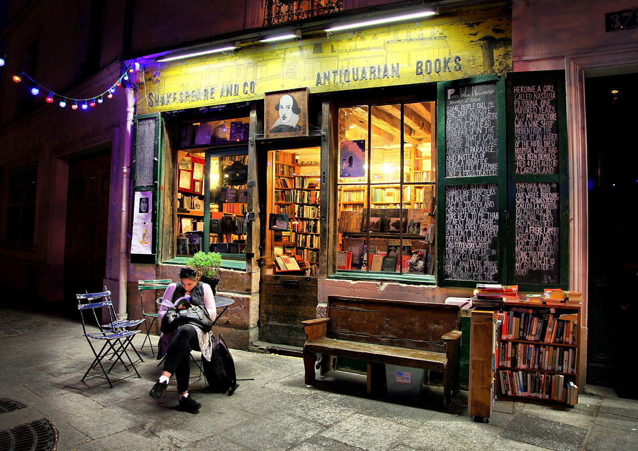 A woman sitting on the patio reading a book outside of a bookstore