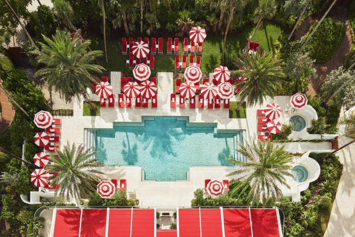 hotel pool with sun umbrellas and palm trees