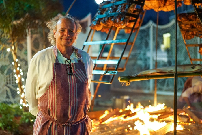 francis mallmann standing in front of open fire cooking