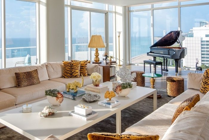 large hotel penthouse with living space and grand piano in the distance