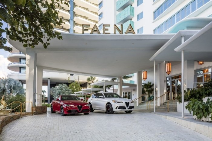 Red and white alfa romeo cars parked in front of Faena hotel
