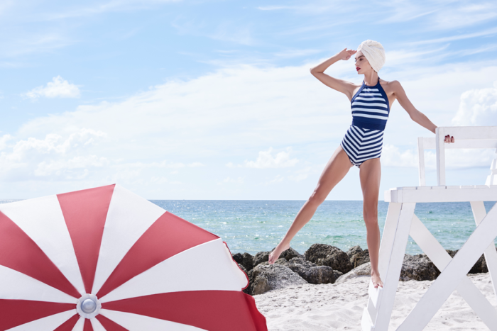 Woman in bathing suit on beach with umbrella