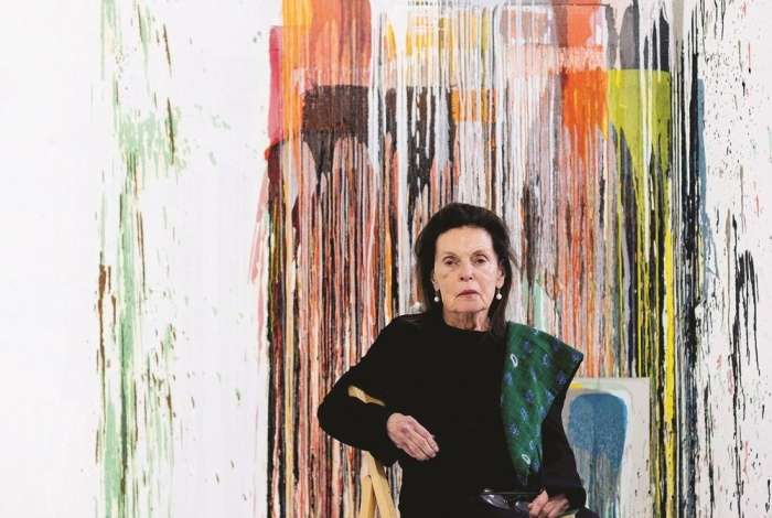 Woman sitting in front of abstract painting