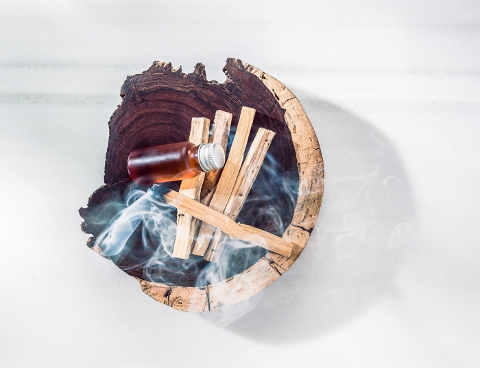 wooden bowl with wood smoking and small bottle