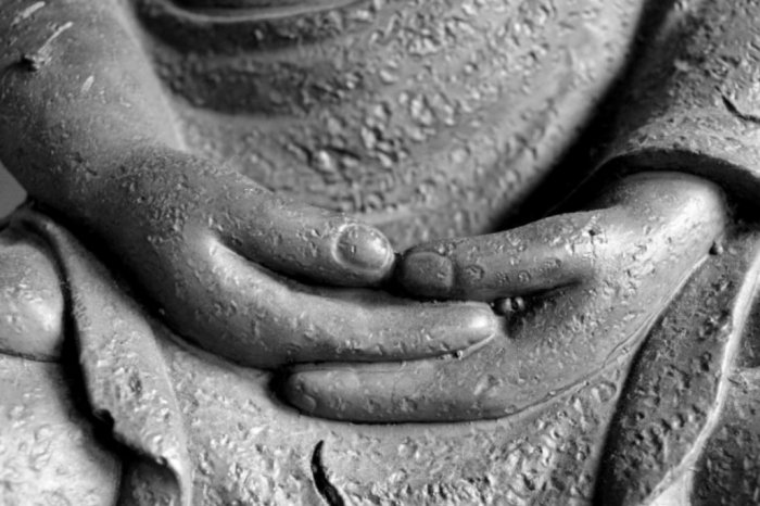Stone hands folded for meditation