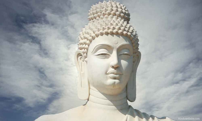 White statue of Buddha with sky and clouds in background