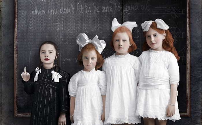 Colorized photo of 4 school girls in front of blackboard