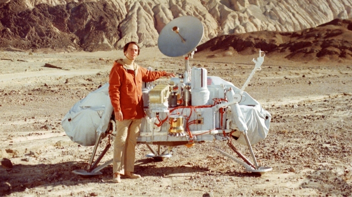 A man standing beside a vintage space rover