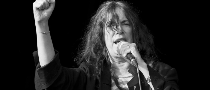Patti Smith speaking into a microphone with her arm raised in a fist