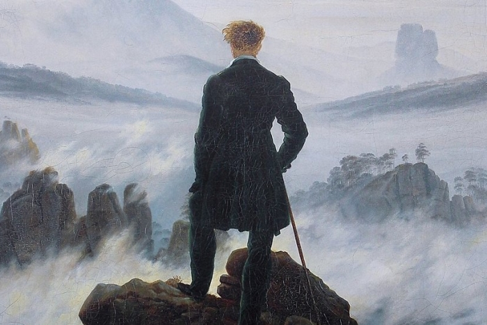 Painting of a man standing on the edge of a foggy cliff