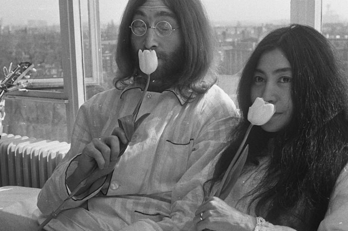 John Lennon and Yoko Ono in bed smelling flowers