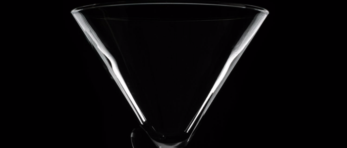 Clear martini glass against black background