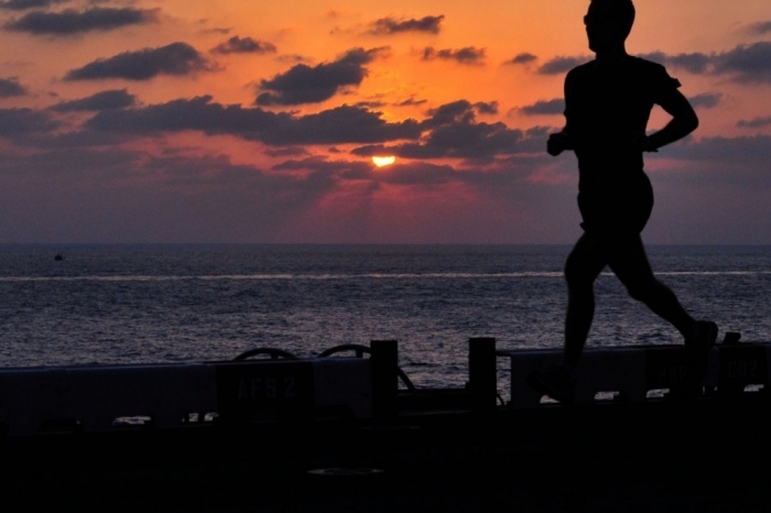 Man running on a boardwalk by the ocean at sunset
