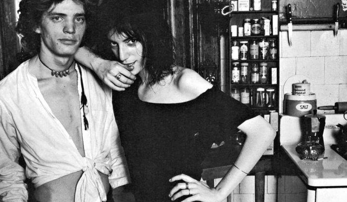 Singer Patti Smith stands with arm on the shoulder of a man.