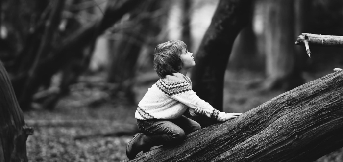 Black and white photo of a young boy climbing on a tree trunk.