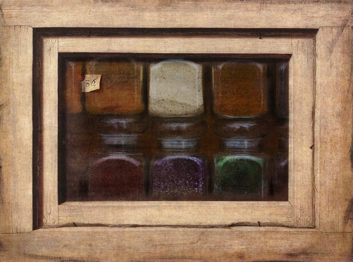 Different glass jars of pigment in a wooden box.