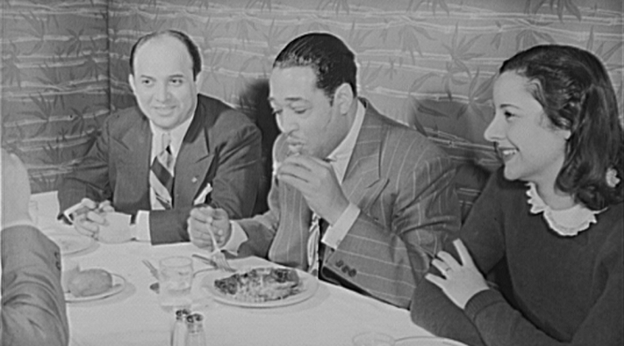 Jazz musician Duke Ellington eating at a restaurant.