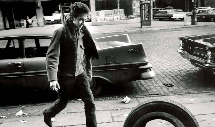 Bob Dylan walking in front of car