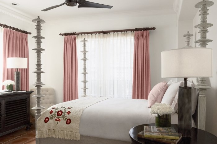 queen bed with four posts and pink curtained windows