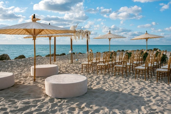 chairs and umbrellas set up on the beach for a wedding ceremony