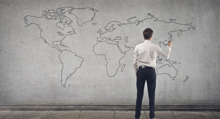 man draws world map on a wall