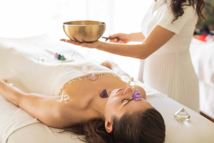 woman lays on table receiving crystal treatment by spa worker