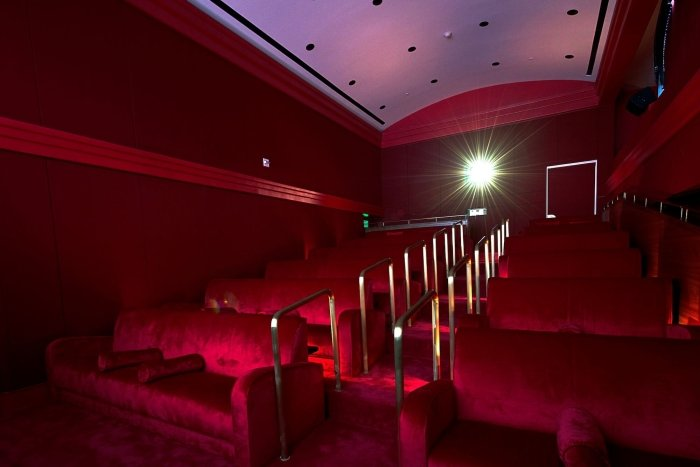 red velvet stairs and movie-theatre style seating with gold handrail with light from projector in background