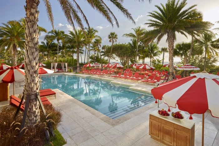 in-ground pool surrounded by red and white umbrellas and lounge chairs with palm trees in background