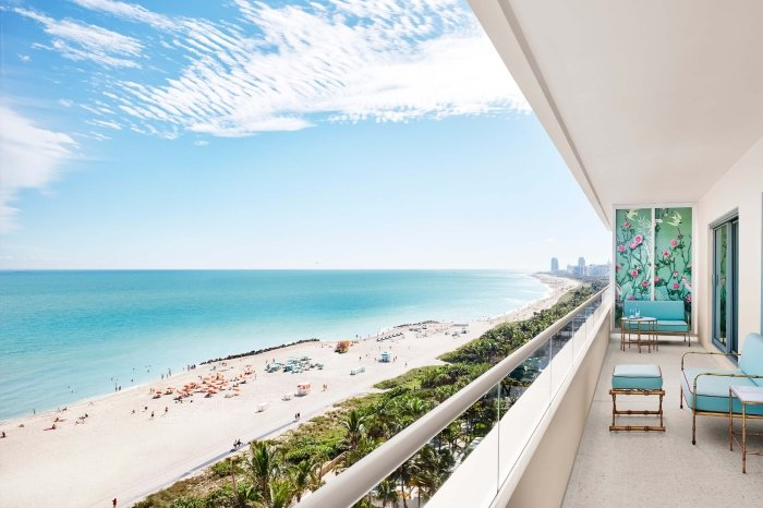 turquoise furniture sits on balcony with beach in the background