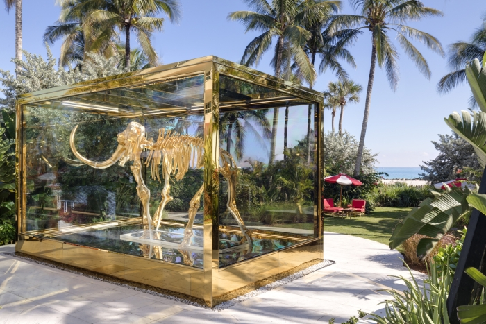 mammoth skeleton inside gold-framed glass case with palm trees and beach in background