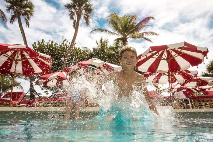 child jumps into pool with red and white umbrellas and palm trees in background