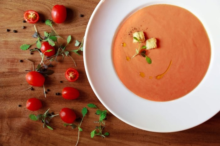 bowl of tomato soup sits on wooden table with sliced cherry tomatoes and greens lay beside it