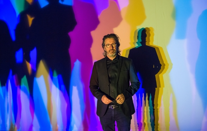 Olafur Eliasson stands in front of multi coloured wall projections