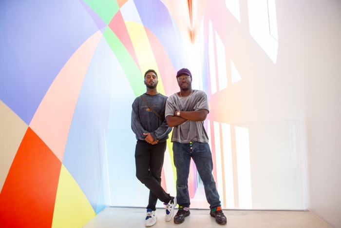 two men stand in front of colorful wall