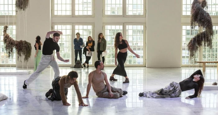 group of performers sit and stand in white walled room mid-performance