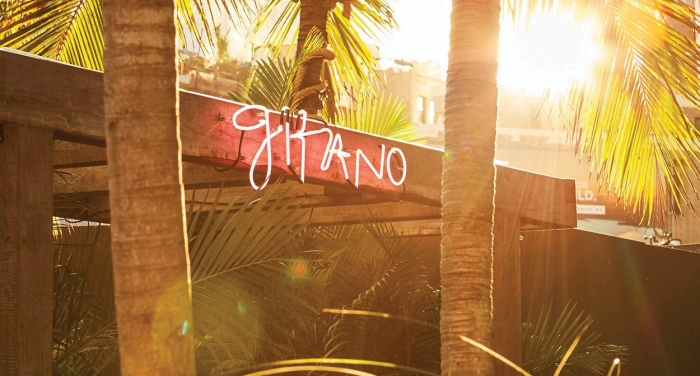 "red neon light reads ""Gitano"" on bulkhead between two palm tree trunks"