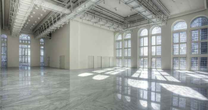 expansive white room with industrial ceiling and floor to ceiling windows