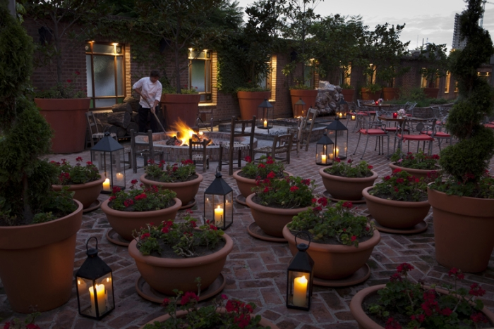 a person in a white coat lights a fire amongst seats and potted plants on outdoor patio