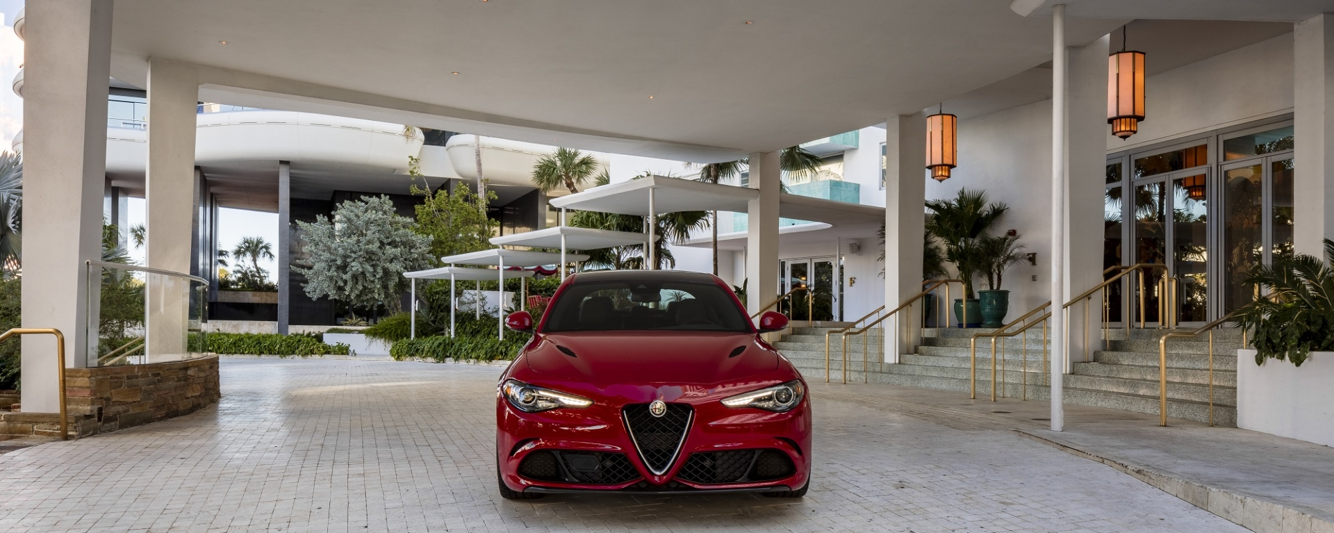 red alfa romeo car parked under Faena sign