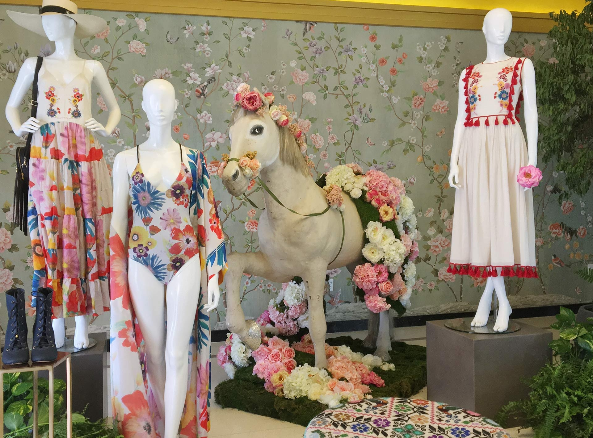 three mannequins in summer clothes and flowers